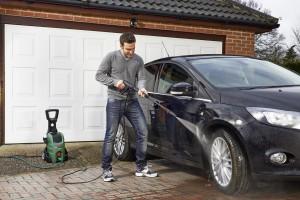 Gli uomini sta lavando la sua auto con idropulitrice acqua calda