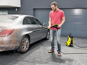 Uomini sorridenti lavare la auto con idropulitrice acqua fredda